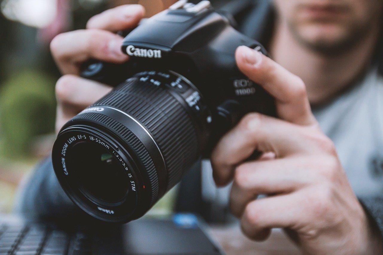 A photographer prepares a Canon as a construction time lapse camera