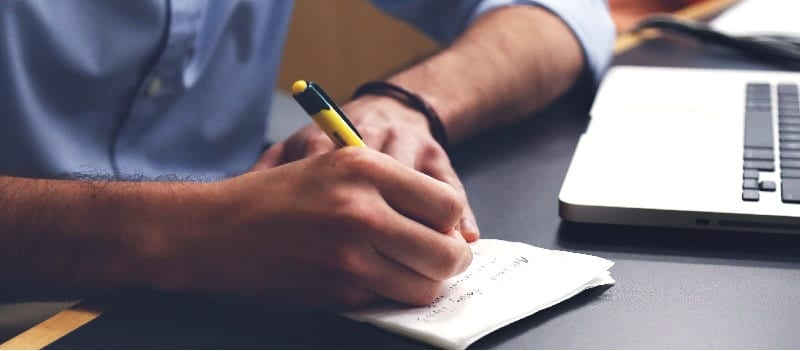 Man's hand writing on notepad next to laptop computer keyboard