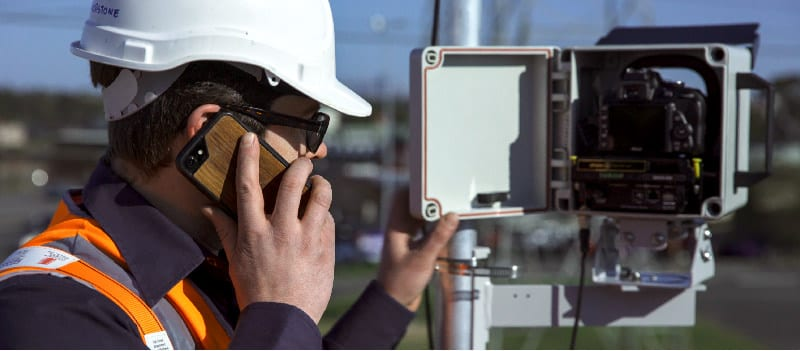A construction worker installs a photoSentinel unit