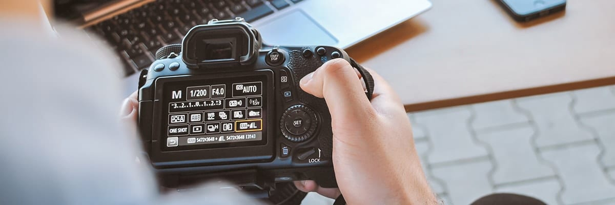 Close-up of hand changing settings on DSLR camera