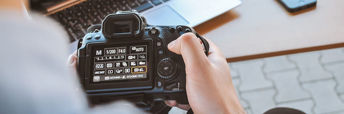 Closeup of hand changing settings on DSLR camera