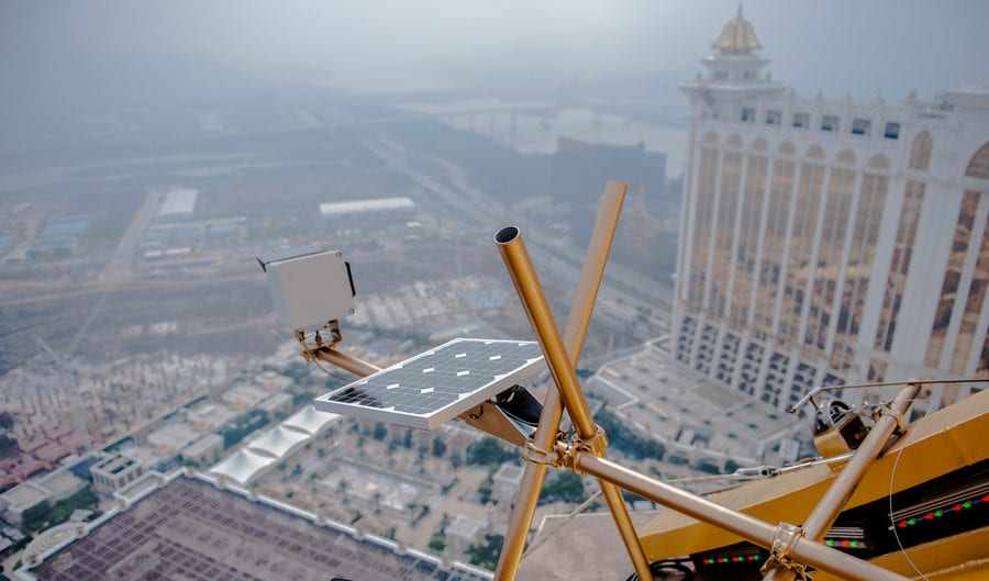 A photoSentinel Mach II long-term timelapse unit mounted on a horizontal pole high above, overlooking a site