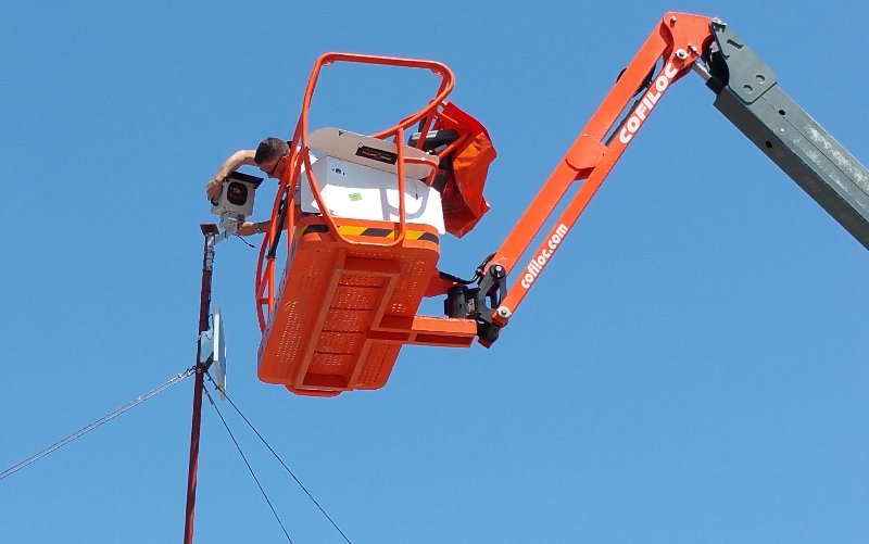 A scissor-lift lifts a worker to install a photoSentinel timelapse system on a pole