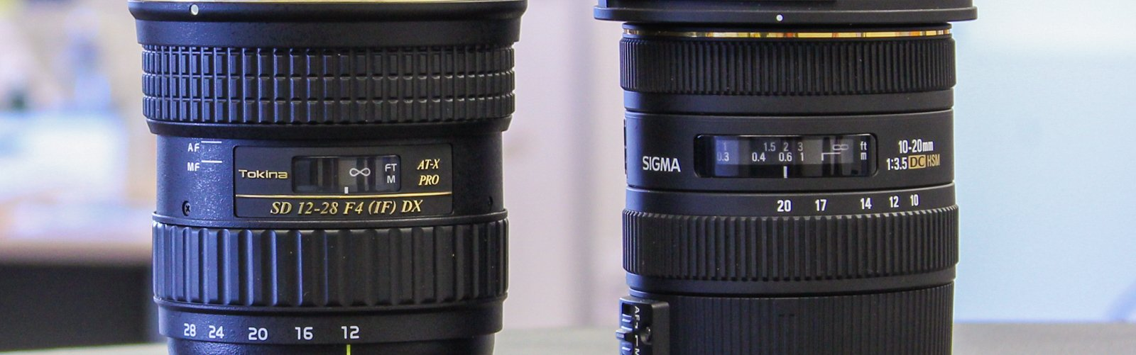 A Tokina and Sigma lens side by side on a table