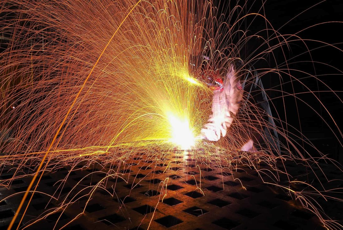 Long exposure photograph of a man welding and welding spark trails