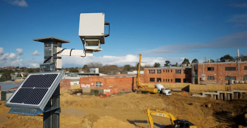 A photoSentinel Mach II with solar panel surveys a dusty construction site